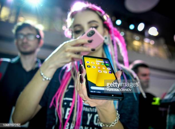 A woman takes pictures of a YandexPhone during a presentation in Moscow on December 5 2018 Russian internet giant Yandex on December 5 2018 launched...