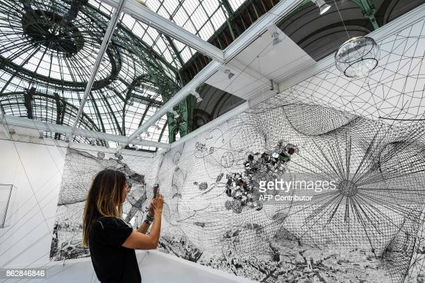 A woman takes pictures of an artwork as she visits the Paris International Contemporary Art Fair at the Grand Palais in Paris during the press...