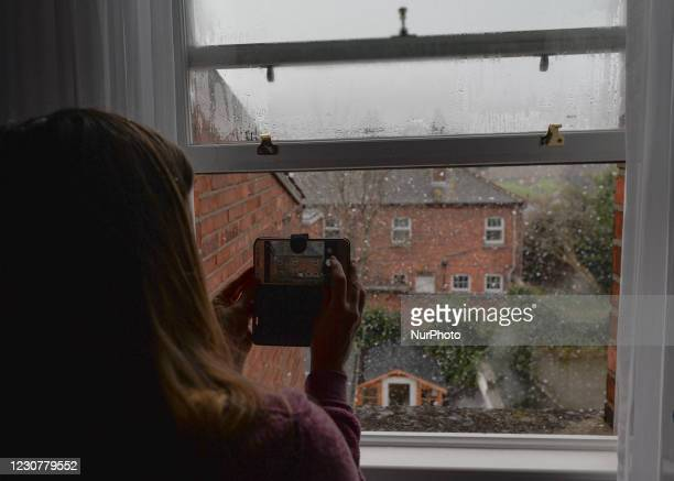 Woman takes pictures of falling snow from her appartment window in Dublin during Level 5 Covid-19 blockade. On Sunday, 24 January in Dublin, Ireland.