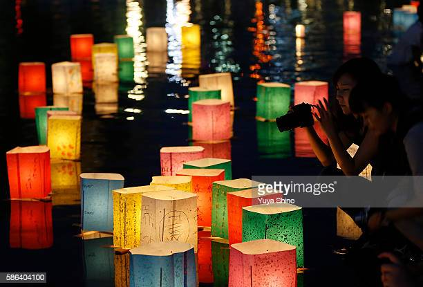 A woman takes pictures of floating candle lit paper lanterns on the river during 71st anniversary activities commemorating the atomic bombing of...