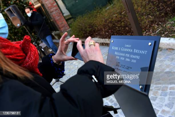 Woman takes pictures of the commemorative plaque during the inauguration ceremony of a square named after late Los Angeles Lakers basketball star...