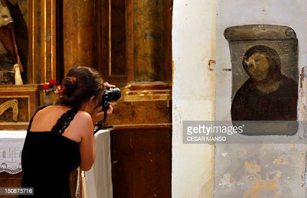 A woman takes pictures of the deteriorated version of 'Ecce Homo' by 19thcentury painter Elias Garcia Martinez at the Borja Church in Zaragoza on...