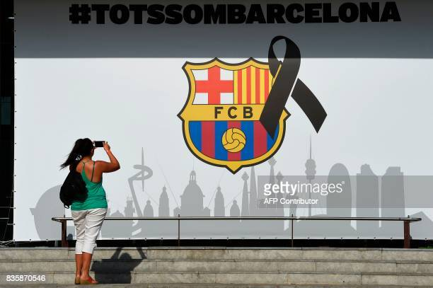 A woman takes pictures of the FC Barcelona logo with a black ribbon and a message reading 'We are all Barcelona' before the Spanish league footbal...