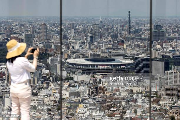 Woman takes pictures of the Olympic Stadium from the Shibuya Sky observation deck in Tokyo on July 21, 2021 ahead of Tokyo 2020 Olympic Games.