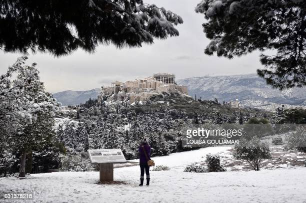 A woman takes pictures of the snowcovered Acropolis from the Pnyx hill in Athens after a rare heavy snowfall on the city on January 10 2017 A cold...