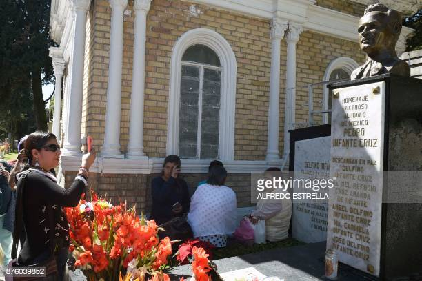 A woman takes pictures of the tomb of Mexican singer and actor Pedro Infante during the 100th anniversary of his birth at the Panteon Jardin in...
