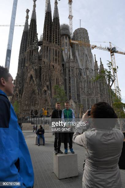 Woman takes pictures of two boys in front of the Sagrada Famila Basilica in Barcelona, on January 3, 2018. The Sagrada Familia basilica, which was...