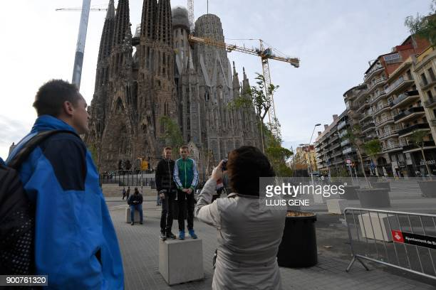 A woman takes pictures of two boys in front of the Sagrada Famila Basilica in Barcelona on January 3 2018 The Sagrada Familia basilica which was...