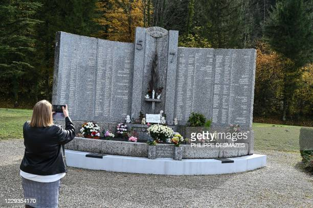 """Woman takes pictures on October 29 in Saint-Laurent-du-Pont, south-east France, at a memorial in tribute to the 146 victims of a fire in the """"5-7""""..."""
