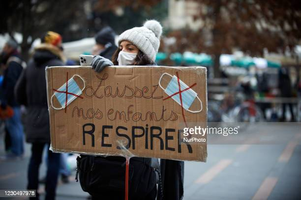 Woman takes pictures while holding a placard reading 'Let's our children breathe'. Parents and children gathered against the sanitary measures in...