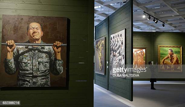 """Woman takes pictures with her mobile phone as she visits an exhibition titled """"Chinese Army. Works by Contemporary Chinese Artists"""" at Saint..."""