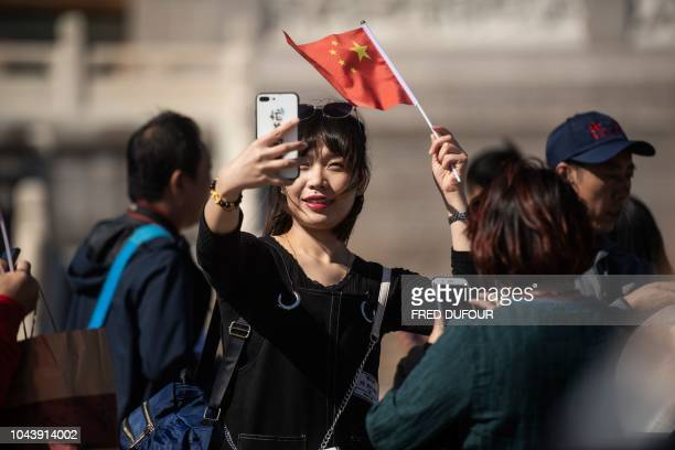 A woman takes pictures with her phone on Tiananmen Square during National Day in Beijing on October 1 2018