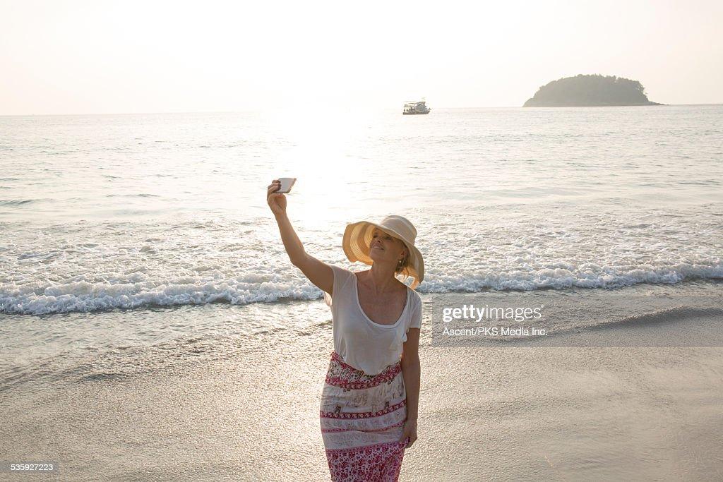 Woman takes selfie at beach edge, sunrise : Stock Photo