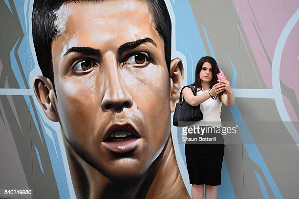 A woman takes selfie in front of Cristiano Ronaldo graffiti ahead of the UEFA Euro 2016 near Hotel de Ville on June 9 2016 in Paris France The...
