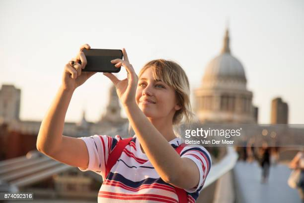 Woman takes selfie on millenium footbridge, st Paul's cathedrale in the background.