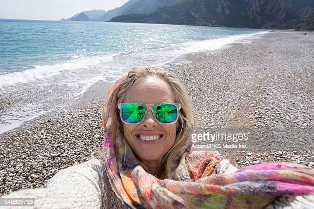 Woman takes selfie portrait on empty beach