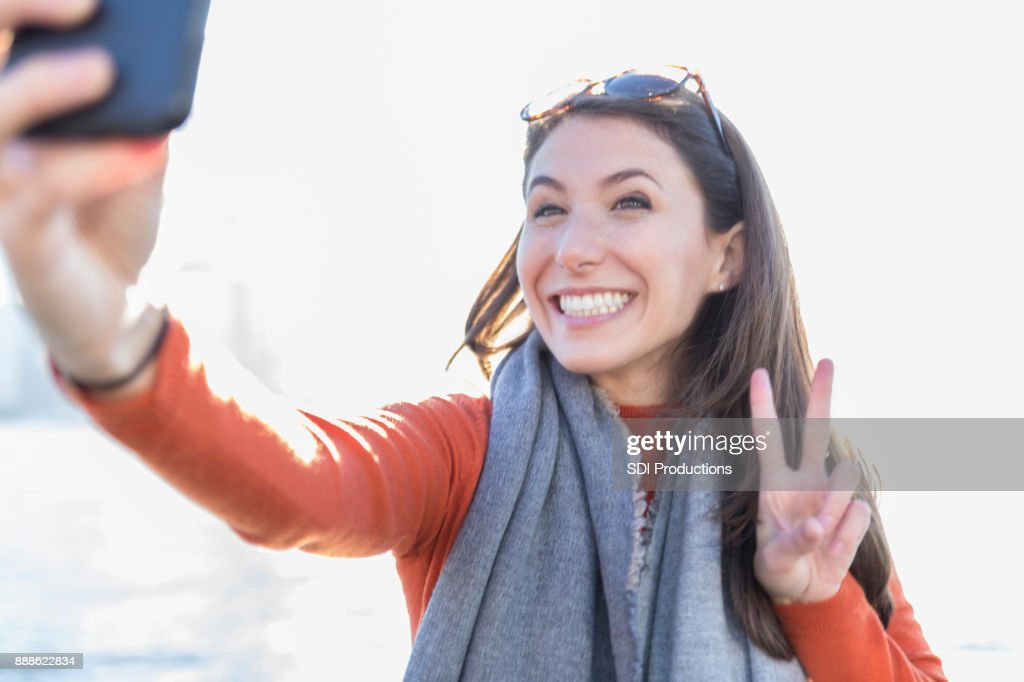 Woman takes selfie while making peace symbol : Stock Photo