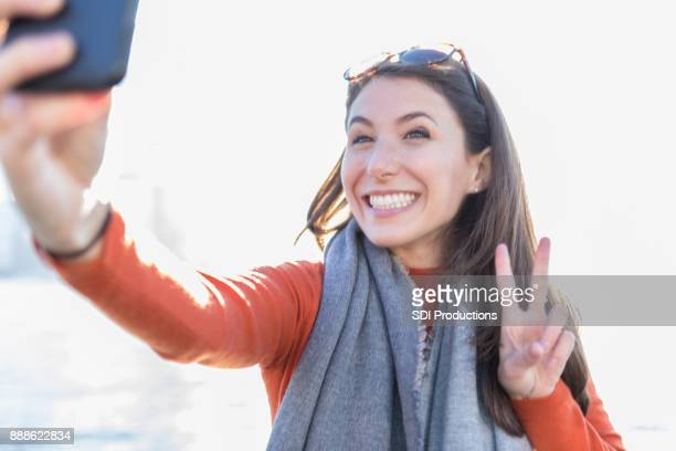 Woman takes selfie while making peace symbol