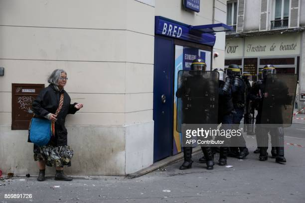 A woman takes shelter along a wall as antiriot police stand near a bank during protests on October 10 2017 in Paris part of a nationwide strikes and...