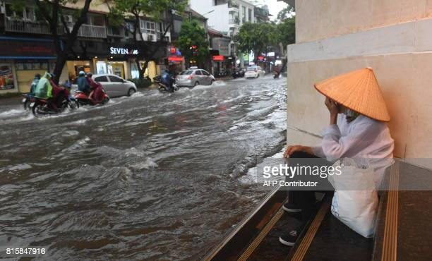 A woman takes shelter from the rain as people commute along a flooded street in Hanoi on July 17 after tropical storm Talas made landfall in northern...