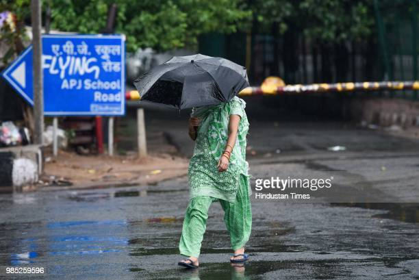 A woman takes shelter under an umbrella during the premonsoon showers near Sheikh Sarai on June 27 2018 in New Delhi India The monsoon rains are...