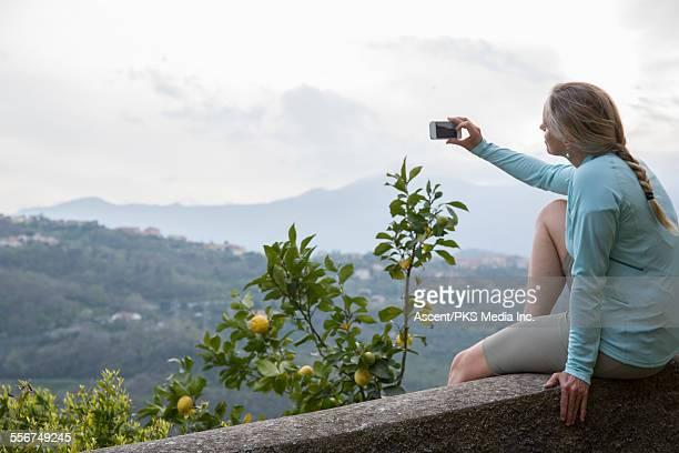 woman takes smart phone pic above lemon tree, hill - maniche lunghe foto e immagini stock