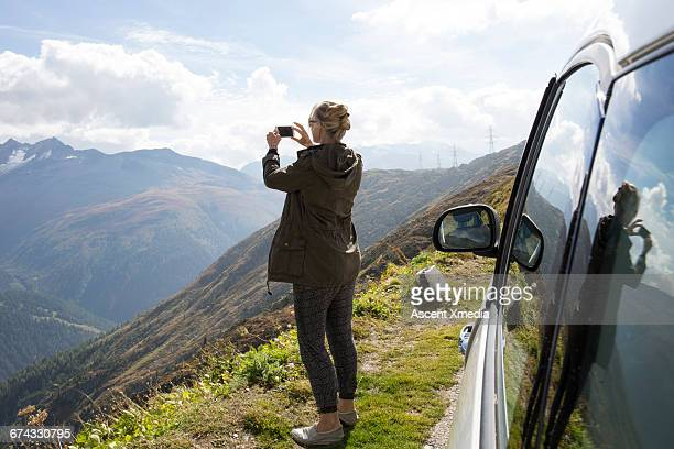 woman takes smart phone pic beside car, mtns - fotografieren stock-fotos und bilder