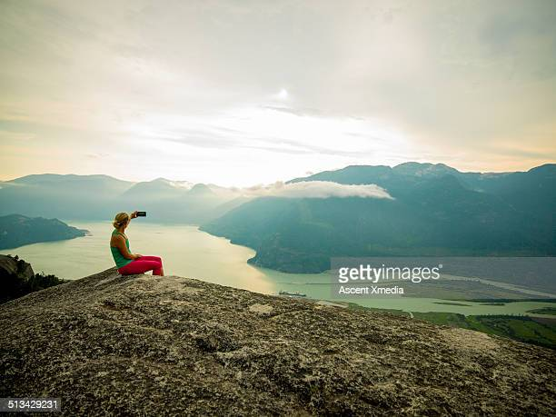 woman takes smart phone pic on mtn summit - photo messaging stock pictures, royalty-free photos & images