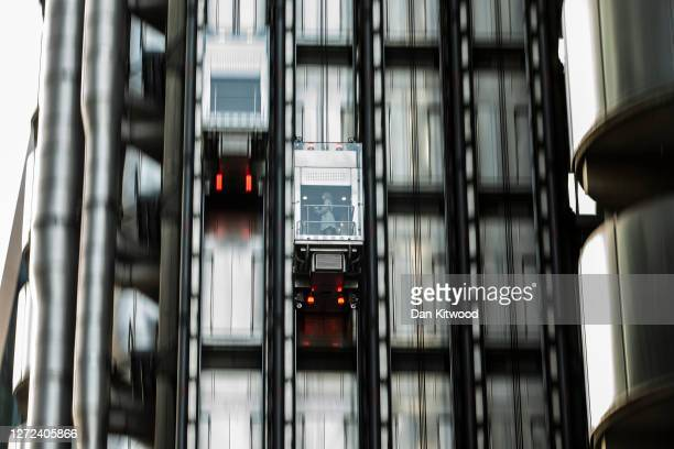A woman takes the elevator wearing a face mask at the Lloyds of London building in the square mile on September 14 2020 in London England Many...