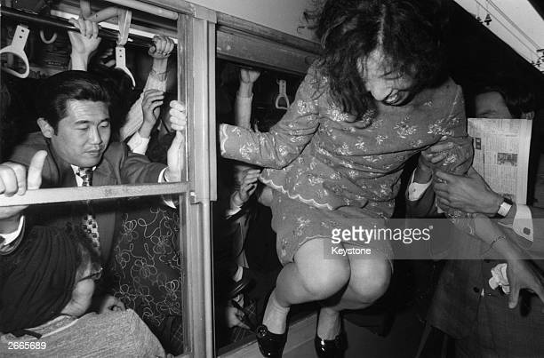 A woman takes the quick exit from a crowded train by climbing out of the window at a Tokyo station The trains are so crowded because of a railway...