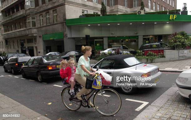 A Woman Takes Two Children To School Using Pedal Power Passing Queues For Petrol Pumps At