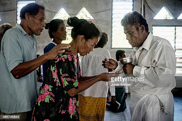 A woman takes values from a Catholic priest Christianity is the dominating religion of the country The people of Kiribati are under pressure to...
