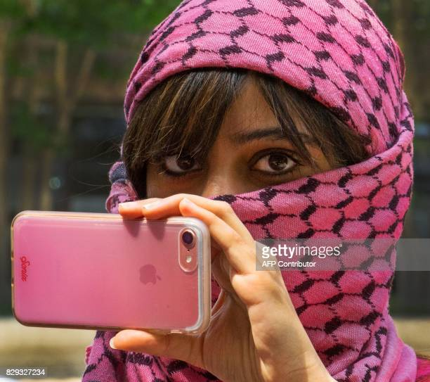 A woman takes video as protesters demonstrate in front of the Saudi Arabian embassy in WashingtonDC on August 10 against the siege of Awamiyah in...