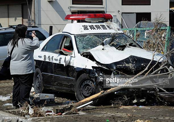 A woman takes video footage of a damaged emergency vehicle deposited in a street in Tagajo Miyagi prefecture on March 13 2011 following a massive...