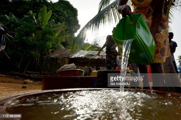A woman takes water from a well in the popular district of Yopougon where inhabitants lack of of drinking water in Abidjan on March 21 2019 a day...