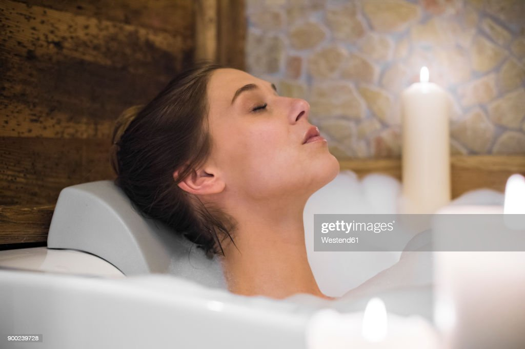 Woman taking a bath in candlelight : Stock Photo