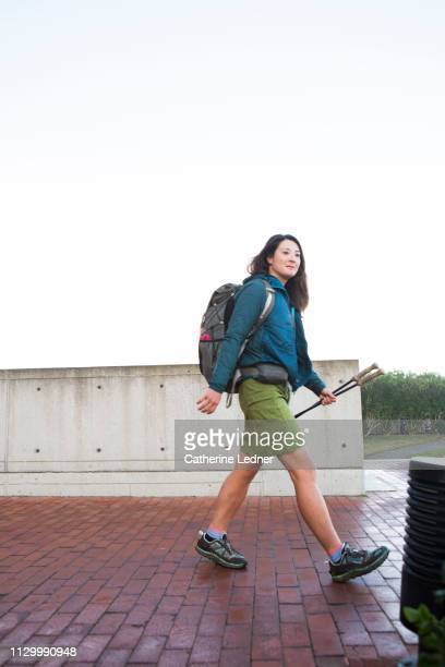Woman taking a big stride forward carrying backpack and walking sticks