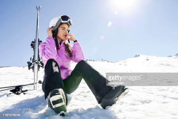 woman taking a break after skiing sitting on the snowy ground in sierra nevada, andalusia, spain - winter sport stock pictures, royalty-free photos & images