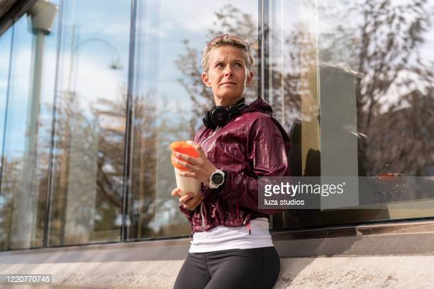 woman taking a break for a protein shake - active lifestyle stock pictures, royalty-free photos & images
