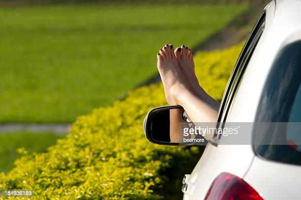 Woman taking a break in the country with feet out car window