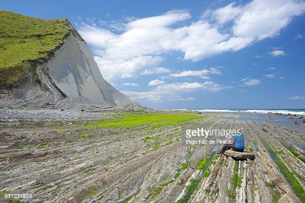 woman taking a break in the flysch - zumaia - guipuzcoa - basque country - spain - pais vasco fotografías e imágenes de stock