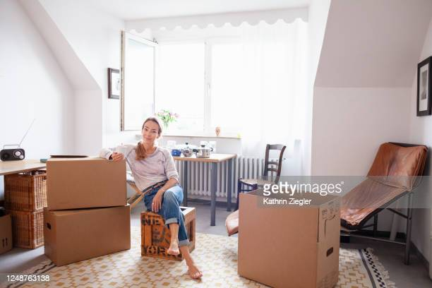 woman taking a break while moving house, sitting on packed boxes - leaning stock pictures, royalty-free photos & images