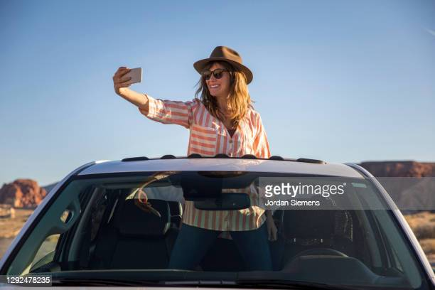 a woman taking a cell phone photo out the sun roof of her car. - western usa stock pictures, royalty-free photos & images