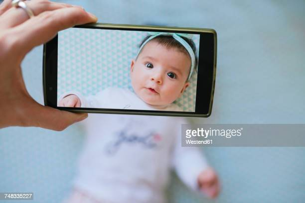 Woman taking a cell phone picture of a baby girl