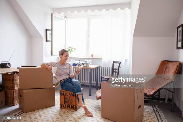 woman taking a coffee break while moving house, text messaging on mobile phone - 引っ越し ストックフォトと画像