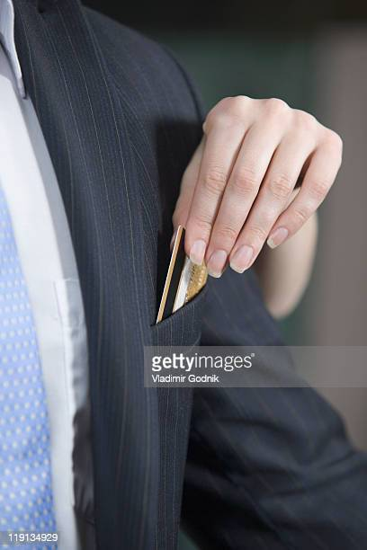 A woman taking a credit card out of a man's jacket pocket
