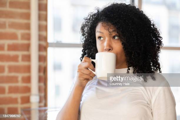 woman taking a drink of coffee from mug - coffee drink stock pictures, royalty-free photos & images