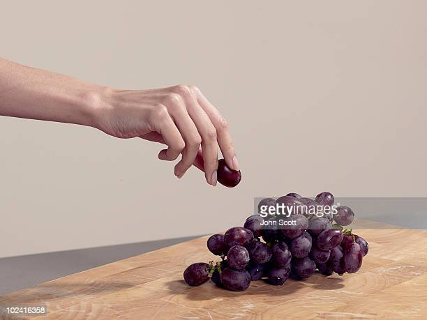 woman taking a grape - reaching stock pictures, royalty-free photos & images