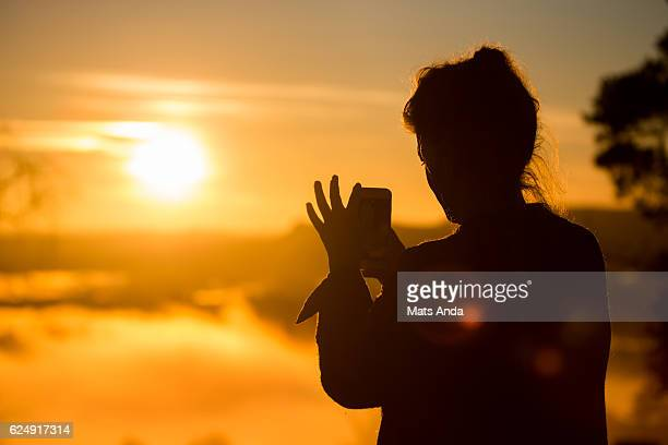 Woman taking a mobile photo of sunset in Oslo, Norway