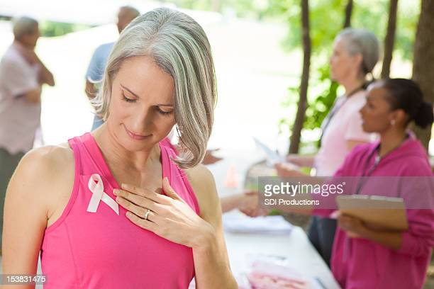Woman taking a moment at breast cancer awareness event.